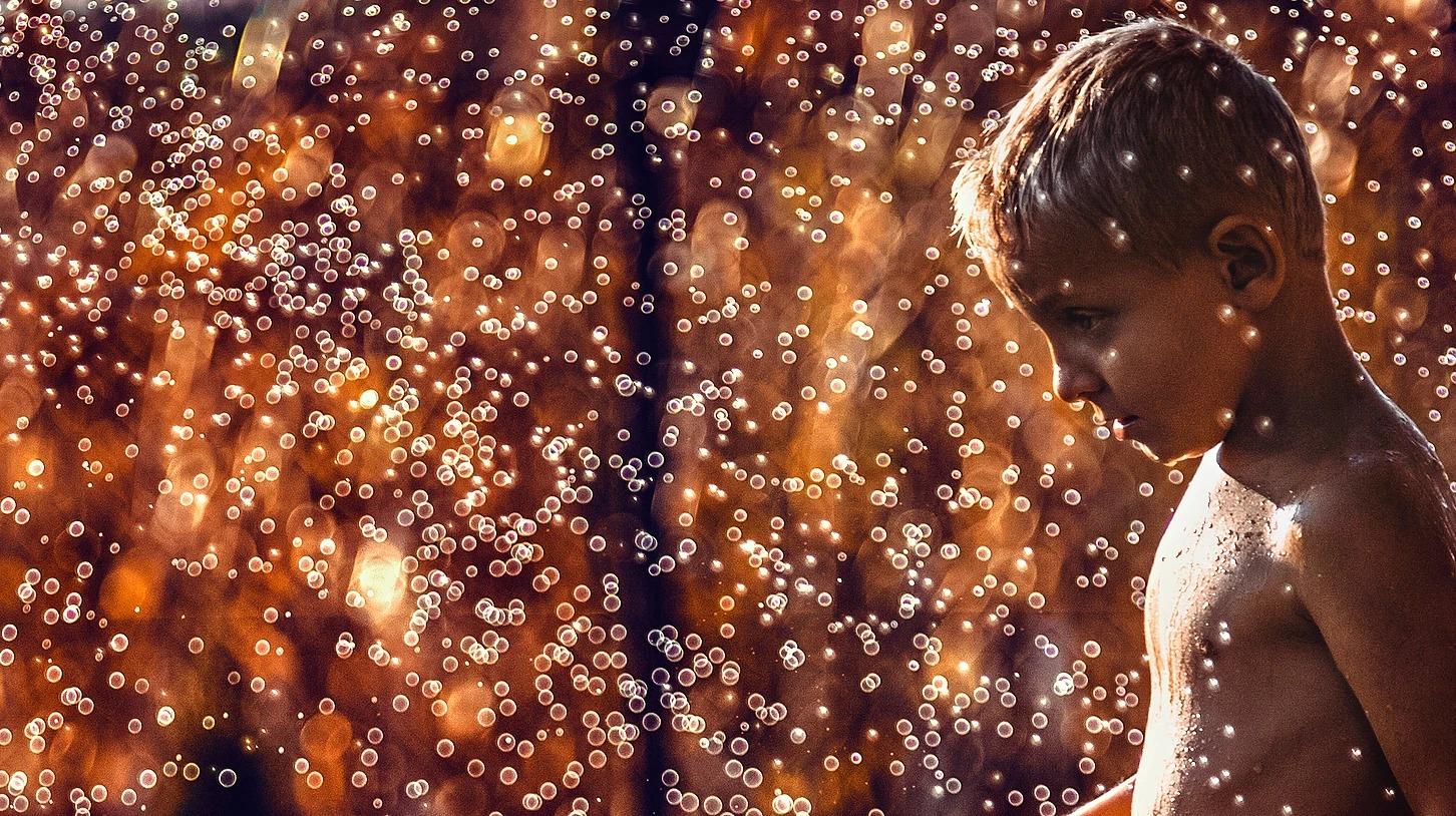Portret chłopca z kroplami wody