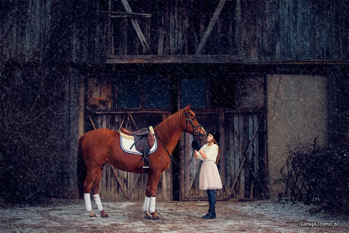 Portret dziewczynki z koniem przed stajnią