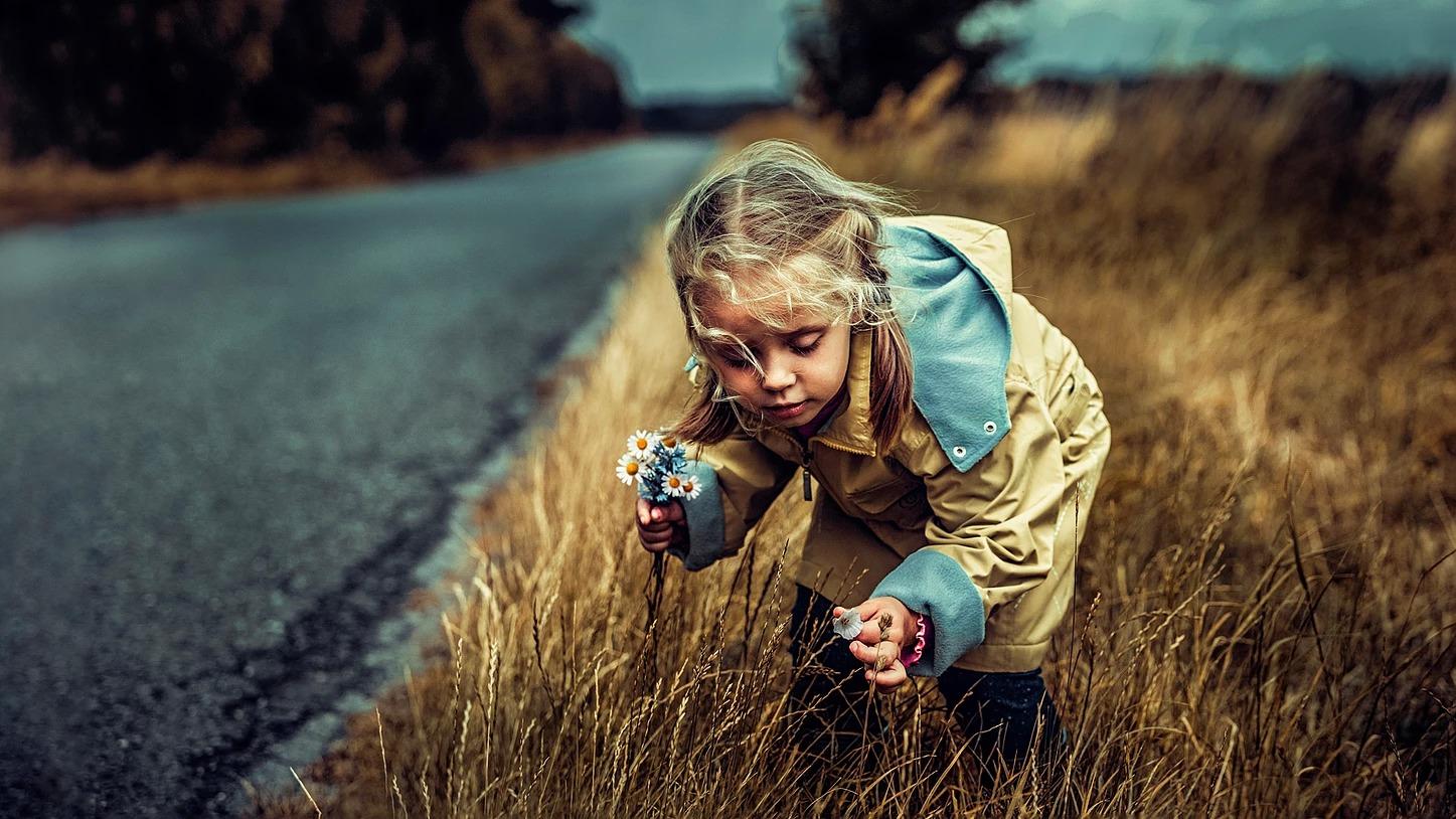 Portret dziewczynki zbierającej kwiatki przy drodze